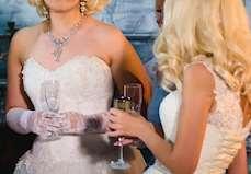 Tre kvinnor i fina klänningar, dyra smycken och med champagneglas i händerna som står och pratar.