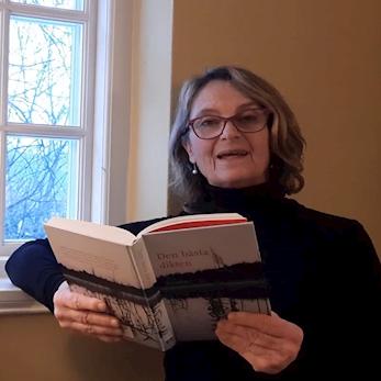Suzanne Reuter står vid ett fönster och läser ur en bok
