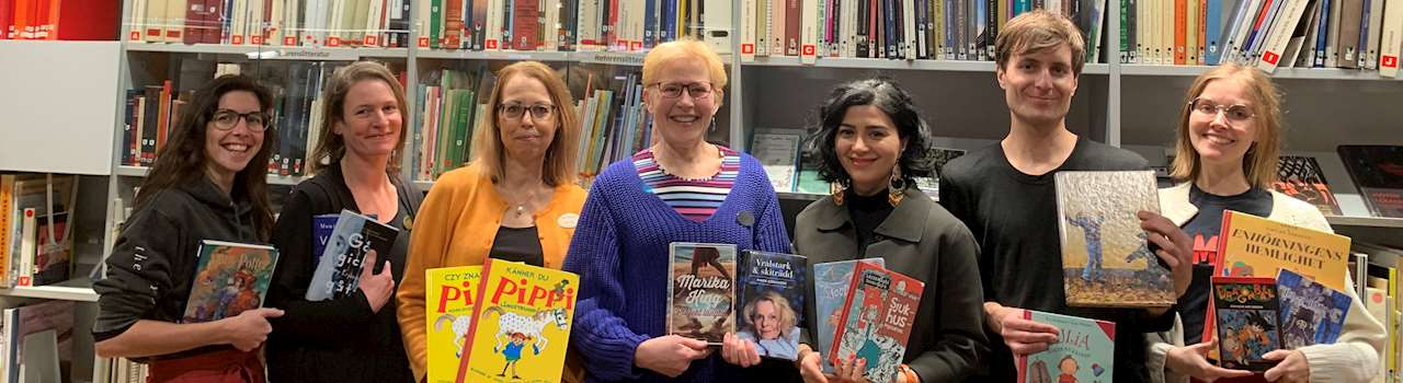 Bild på bibliotekets personal som håller upp boktips