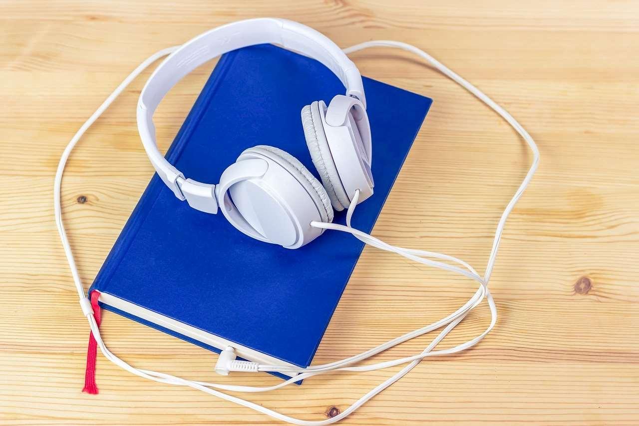 Bild på hörlurar kopplade till en blå bok