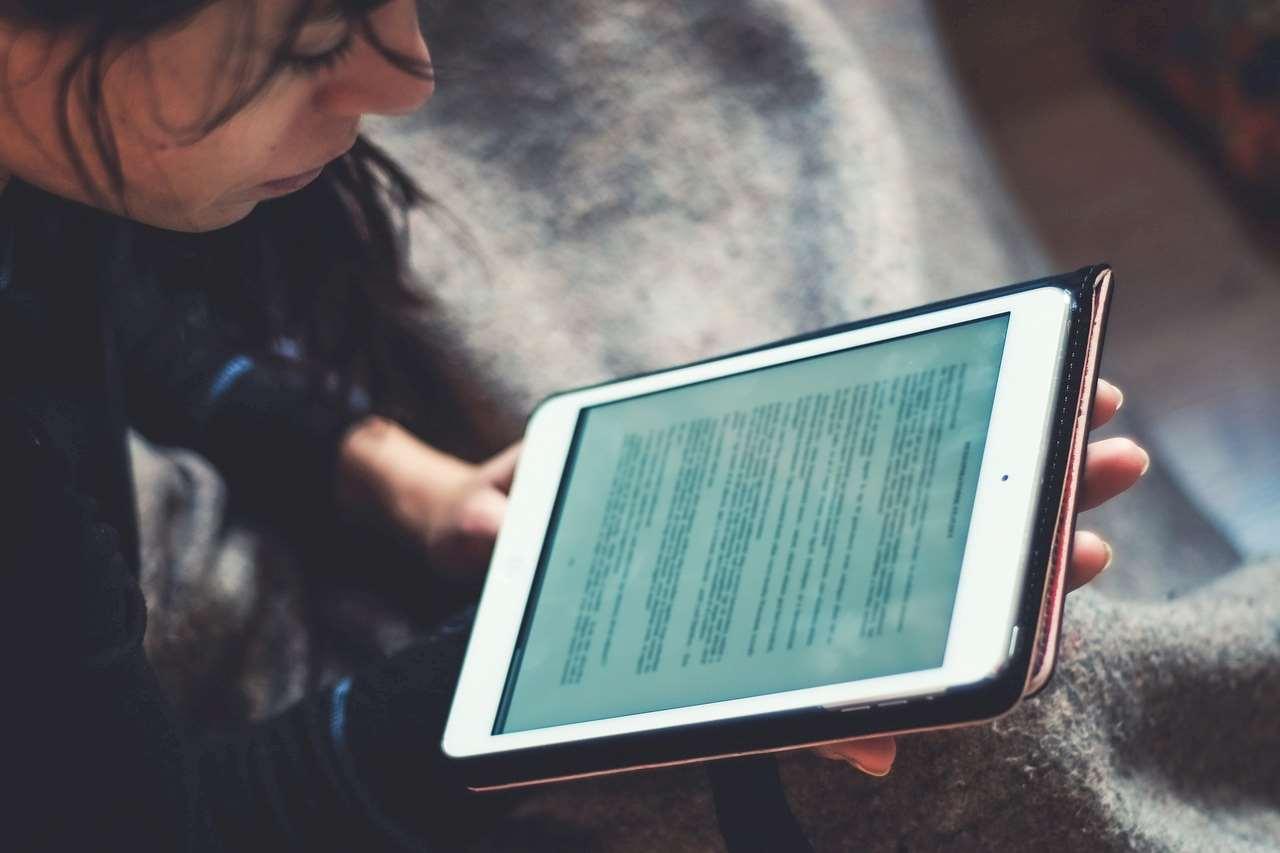 Bild på ett barn som läser på en läsplatta